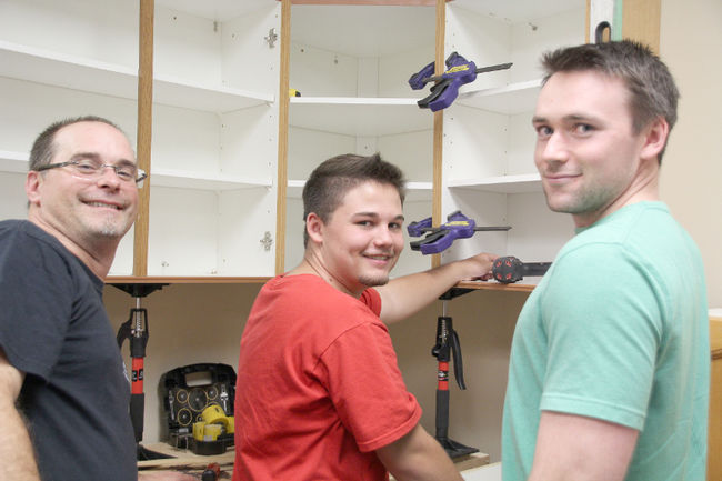 Picture from the Orillia packet and times. Owner Terry Barkey with little brothers installing a donated kitchen